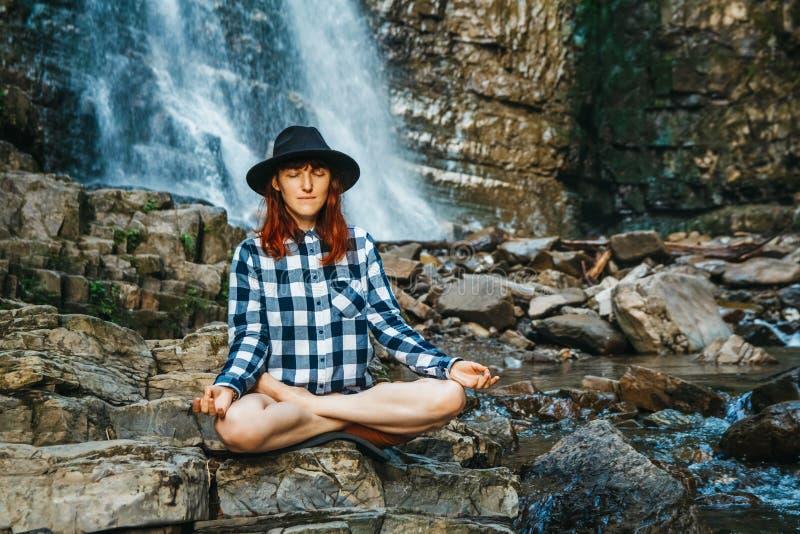 有红色头发的美女在帽子和衬衣思考在莲花坐的岩石的反对瀑布 空间为 免版税库存照片
