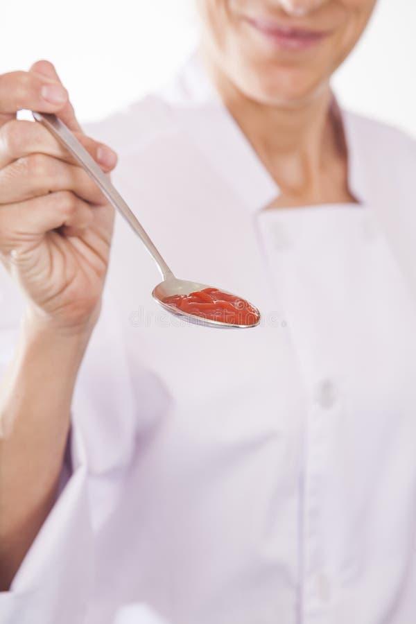 有红色奶油的厨师手提供的匙子 库存照片