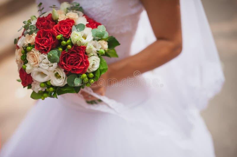 有红色婚礼花束的新娘 库存图片