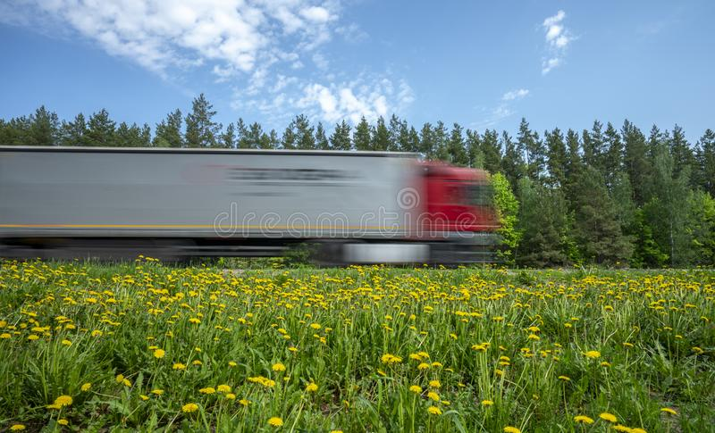 有红色小室的一辆卡车沿沿森林的路冲,路旁用黄色蒲公英盖 库存图片