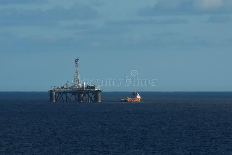 有红色小船的海洋平台在开放海洋 免版税图库摄影