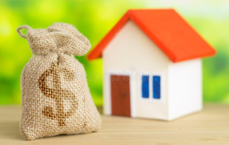 有红色屋顶的一个家在与袋子的绿色背景从有美元的符号的在出售或购买家里面的袋子概念的大袋和金钱 图库摄影