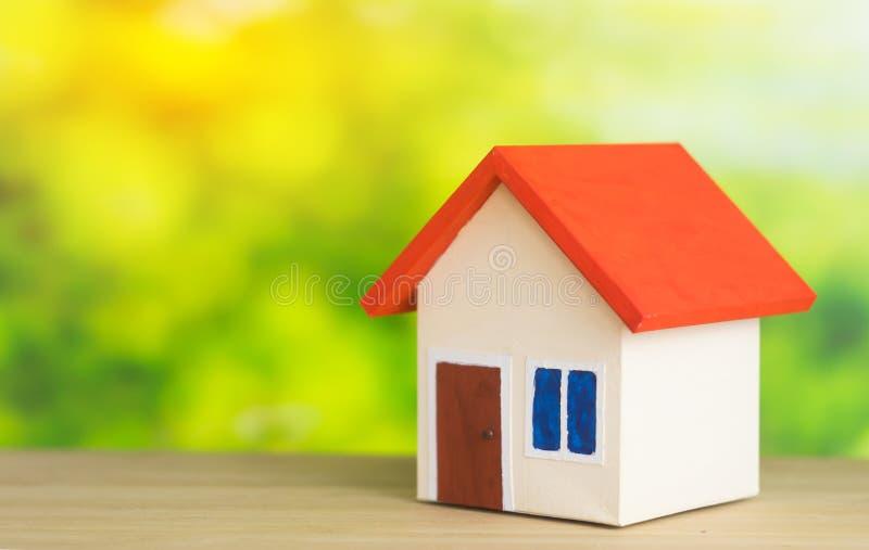 有红色屋顶的一个家在出售或购买家的绿色背景概念 库存图片