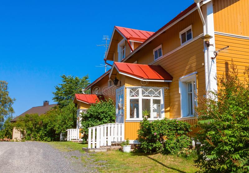 有红色屋顶的木黄色房子在斯堪的纳维亚样式 免版税库存照片