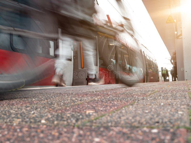 有红色市郊火车的路轨平台在行动迷离,有在前景弄脏的话筒的人 库存图片