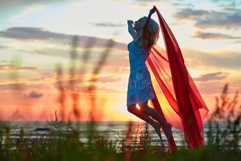 有红色布料的跳跃的女孩 免版税库存照片