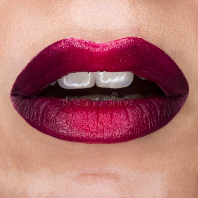 有红色席子唇膏的特写镜头宏观美丽的嘴唇 红色梯度、白色牙和开放嘴 嘴唇艺术 库存图片