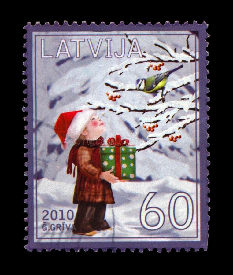 有红色帽子、绿色箱子有礼物的和鸟tomtit的男孩在冬天树,大约2010年, 免版税图库摄影