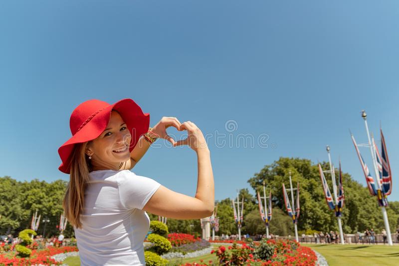 有红色帽子框架花的妇女到心形,手指心脏框架里 看和微笑对照相机 库存图片