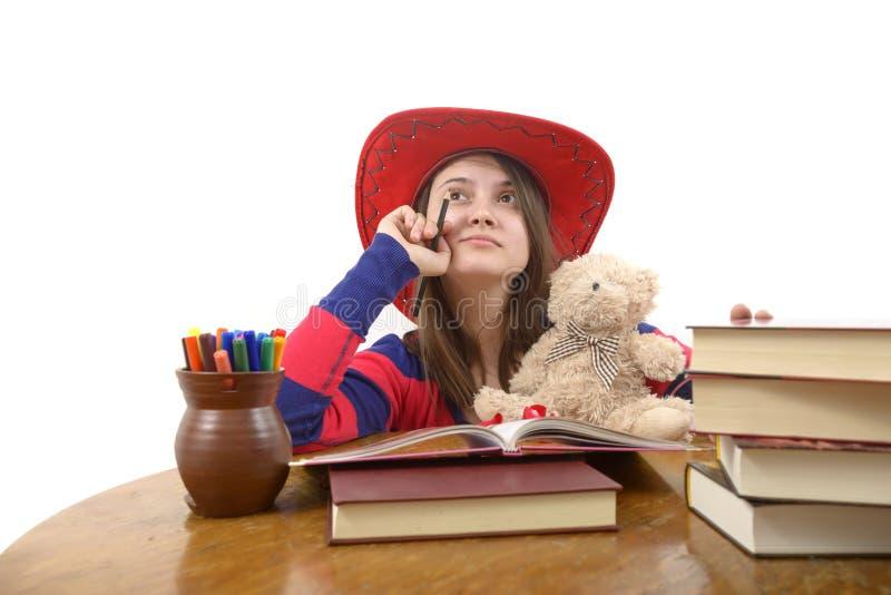 有红色帽子的年轻冥想的女孩和她的玩具熊在桌上 库存图片