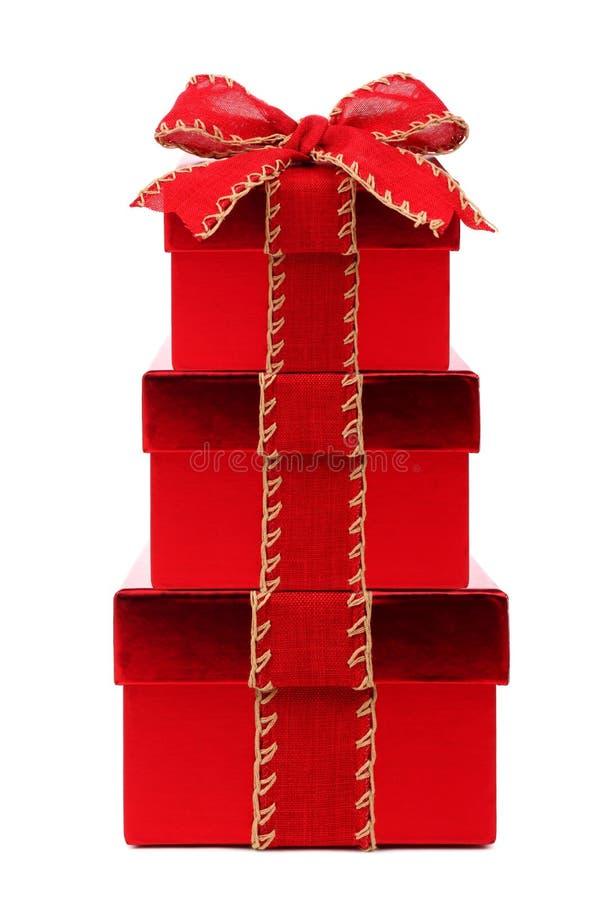 有红色弓和丝带的被堆积的红色圣诞节礼物盒在白色 免版税库存图片