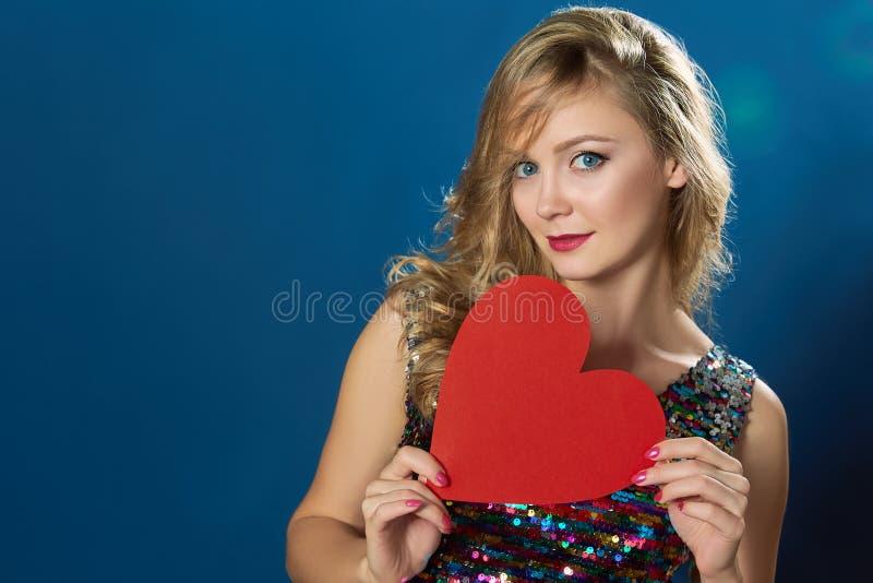有红色心脏的华伦泰白肤金发的妇女 免版税图库摄影