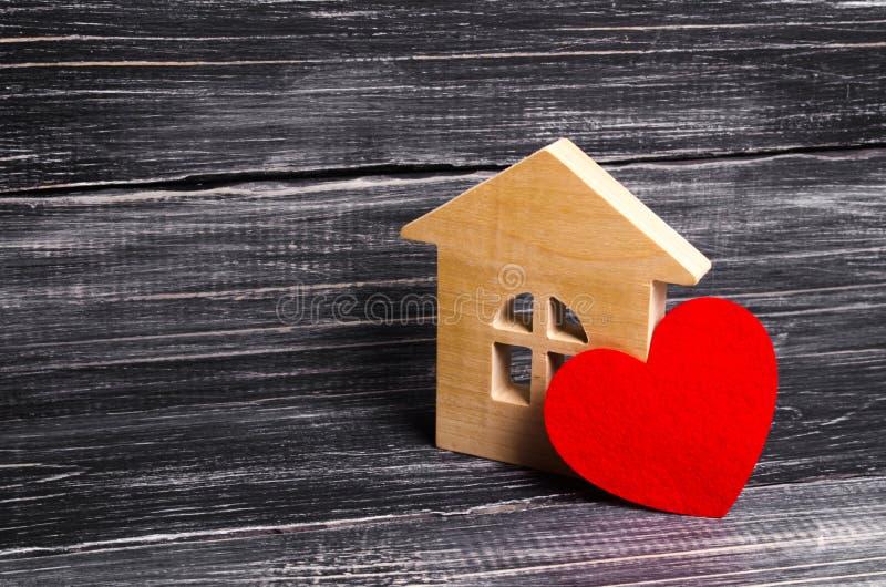 有红色心脏的木房子在黑暗的木背景 恋人的一个房子,蜜月 购买您自己付得起的住房 免版税库存照片