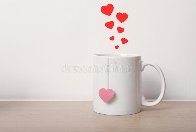 有红色心脏的白色茶杯在木桌上 免版税库存照片