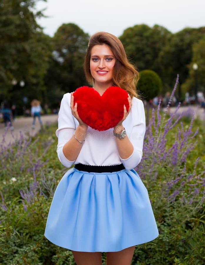 有红色心脏的美丽的时兴的女孩在公园在温暖的夏天晚上 免版税库存照片