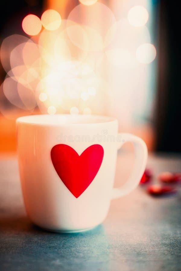 有红色心脏的舒适杯子在bokeh照明设备背景,正面图的桌上 爱标志或情人节 库存图片