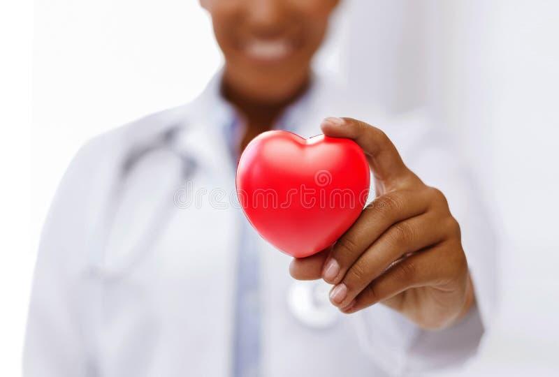 有红色心脏的非洲女性医生 免版税库存图片