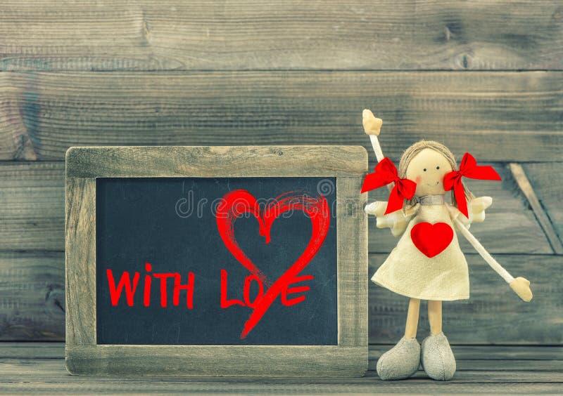 有红色心脏的滑稽的女孩 充满爱的情人节balckboard 免版税库存照片