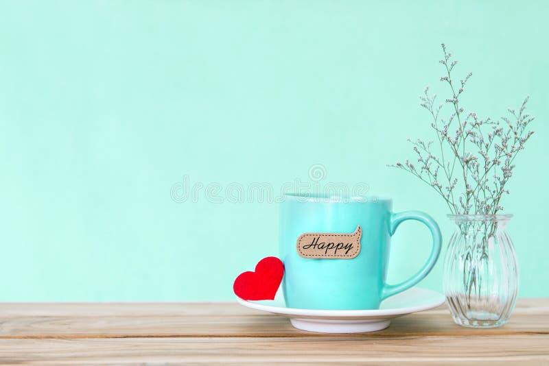 有红色心脏shapeand愉快的词标记的咖啡杯杯子在木 免版税库存照片