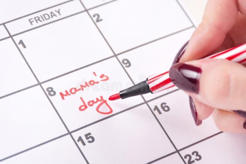 有红色感觉的笔的妇女手在日历写词妈妈天 库存照片