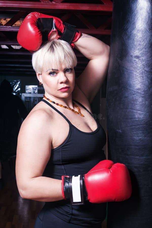 有红色拳击手套的美丽的妇女,在沙袋旁边 免版税库存照片