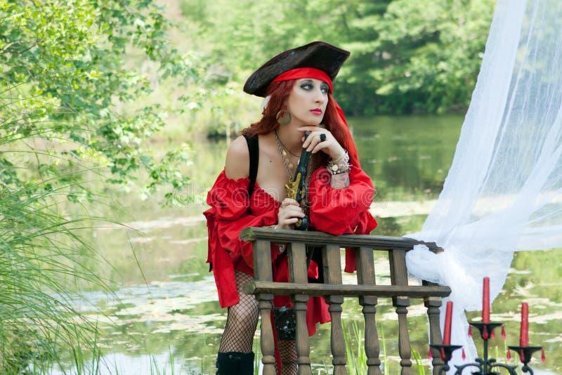 有红色方巾的女性海盗女孩在有海盗手枪的小船 库存图片