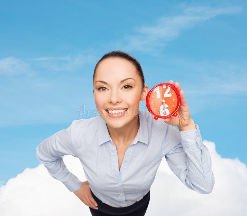有红色时钟的微笑的女实业家 免版税库存照片