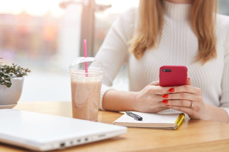 有红色智能手机的无法认出的妇女在她的手,键入的消息上,工作在网上在自助食堂,有笔记本,笔, 免版税库存图片
