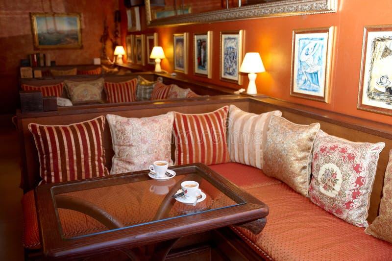 有红色枕头和木桌的空的沙发在咖啡馆 老古家具,破旧的别致的外部 例证百合红色样式葡萄酒 免版税库存照片