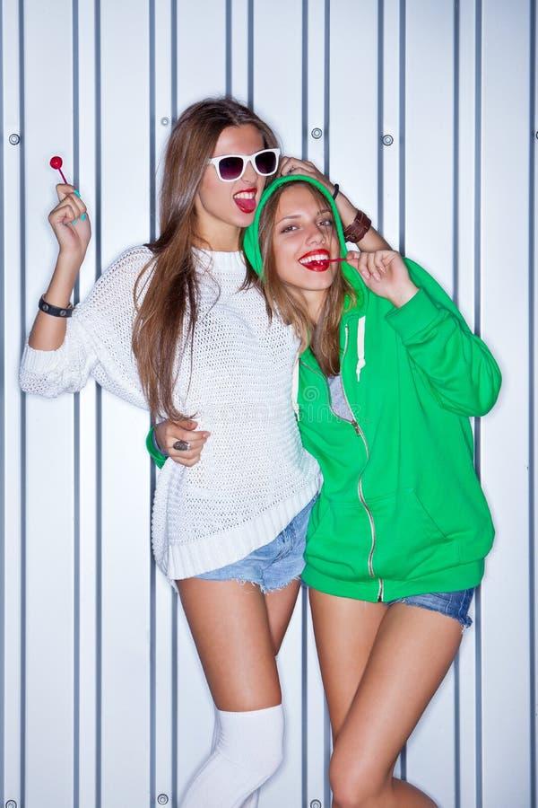 有红色棒棒糖的二个美丽的女孩在墙壁附近 库存图片