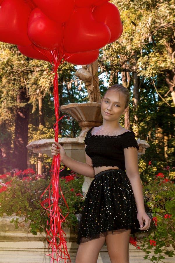 有红色气球的华伦泰美丽的少女在公园笑, 美丽的愉快的孩子 圣诞晚会 快乐的小的模型 库存照片