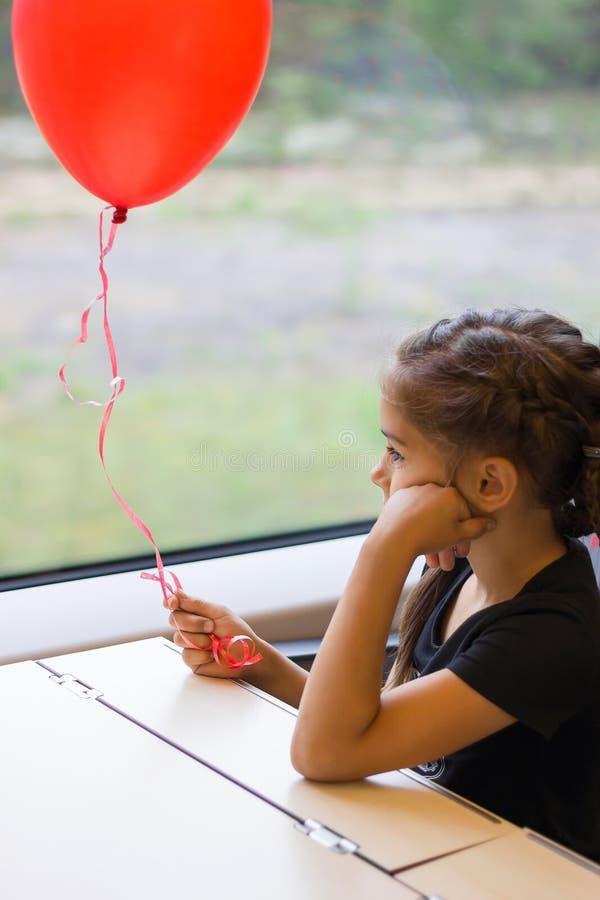 有红色气球的哀伤的沉思女孩在她的看火车窗口的手上 库存照片