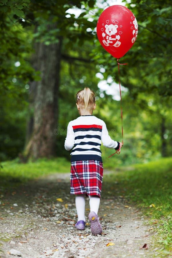 有红色气球的小白肤金发的女孩走在小径的。 免版税库存图片