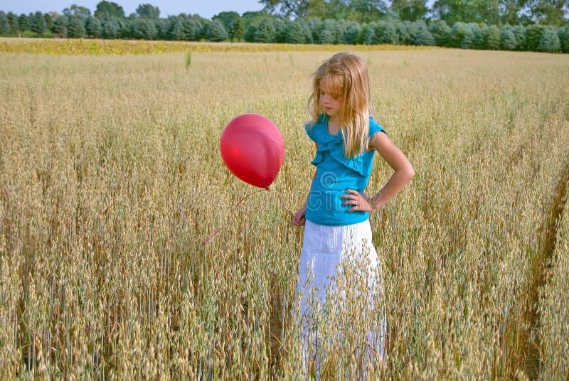 有红色气球的少女在麦子 库存图片