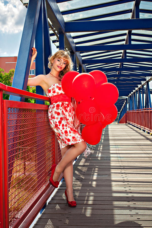 有红色气球的少妇在桥梁 图库摄影