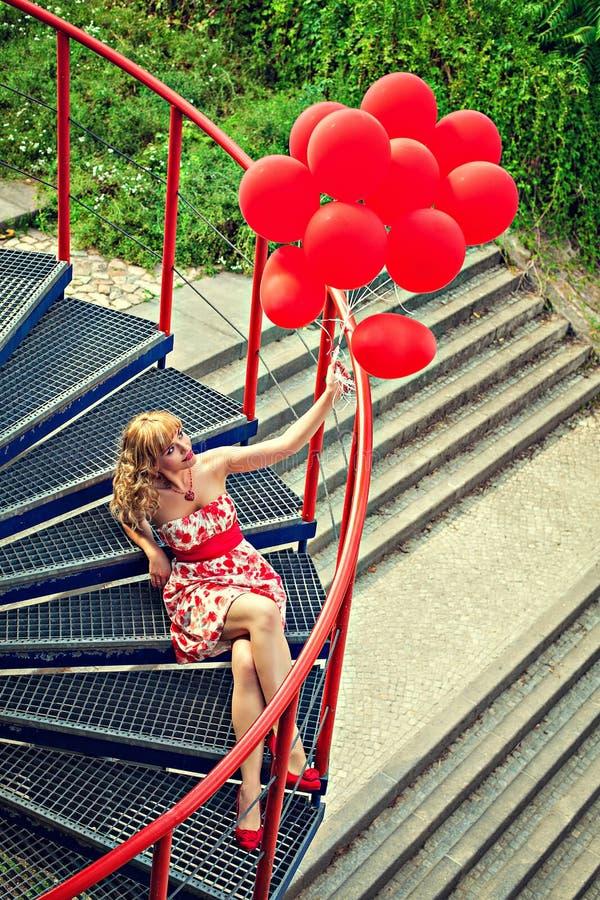 有红色气球的少妇坐步 免版税库存图片