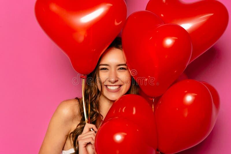有红色气球的愉快的妇女 库存照片