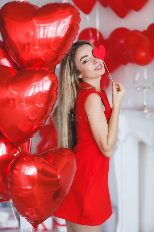 有红色气球的美丽的聪慧的妇女在华伦泰` s天 免版税库存照片