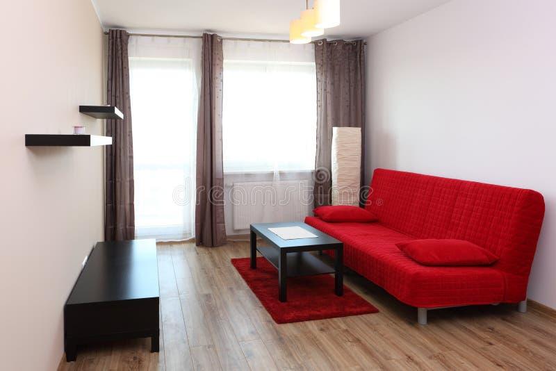 有红色沙发的室 库存图片