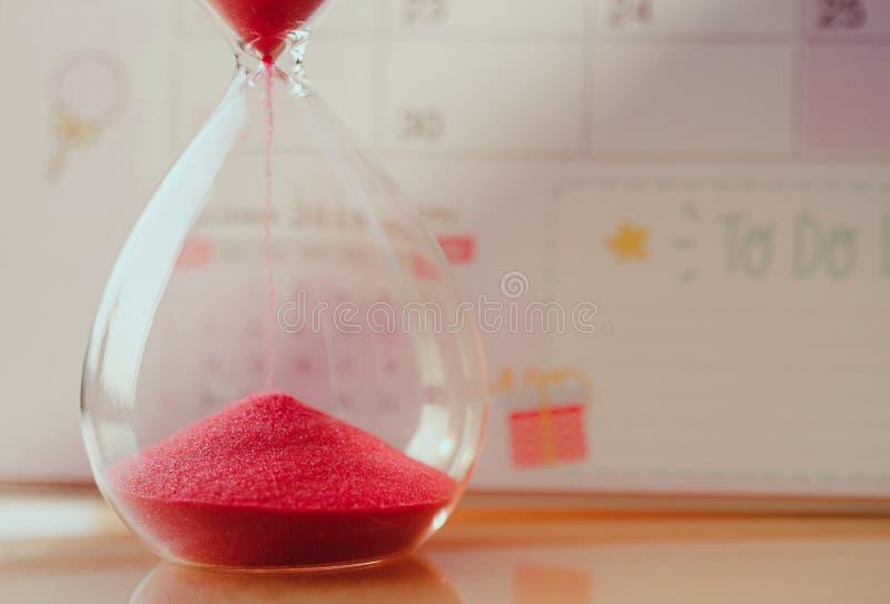 有红色沙子的水晶滴漏在滑倒的时刻的日历概念的重要任命日期 免版税库存照片