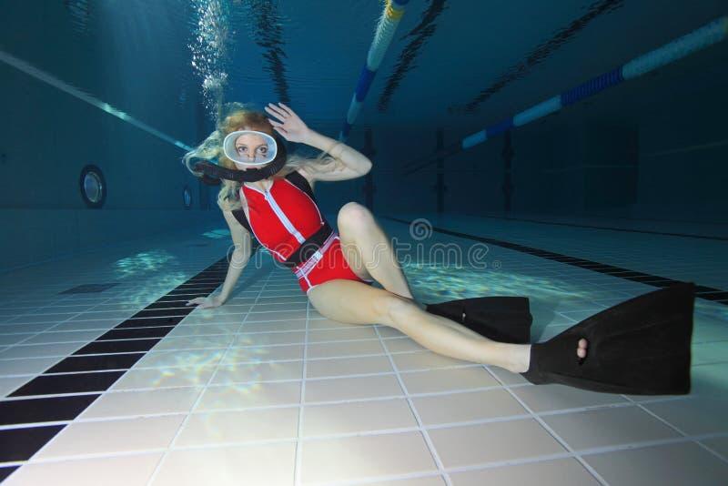 有红色泳装的女性轻潜水员 图库摄影