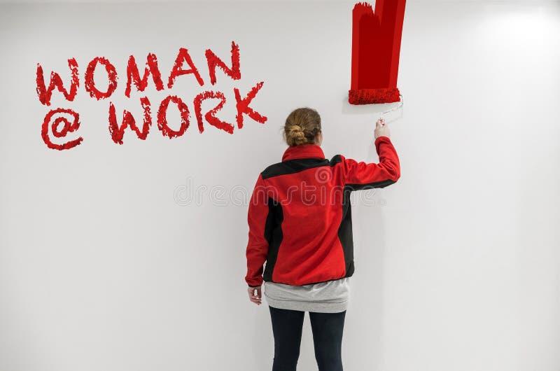 有红色漆滚筒的女性画家在作为templat的墙壁前面 库存照片