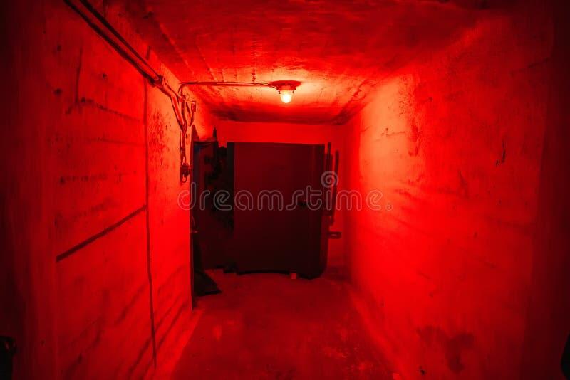 有红色照明的在防空洞,冷战地下军事地堡的走廊和大铁或钢门或者门  免版税库存图片