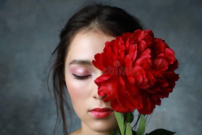 有红色牡丹和红色口红的美丽的新鲜的亚裔妇女 免版税图库摄影