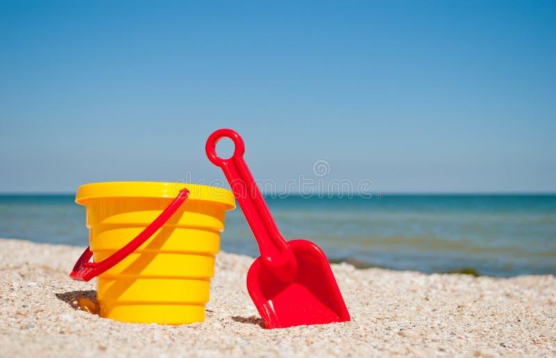 有红色玩具玩具红色塑料小铲的黄色婴孩桶在左边反对蓝色海海沙夏天晴天,婴孩戏弄 免版税库存图片