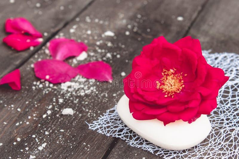 有红色玫瑰和瓣的天然化妆品肥皂在黑暗的木背景 图库摄影