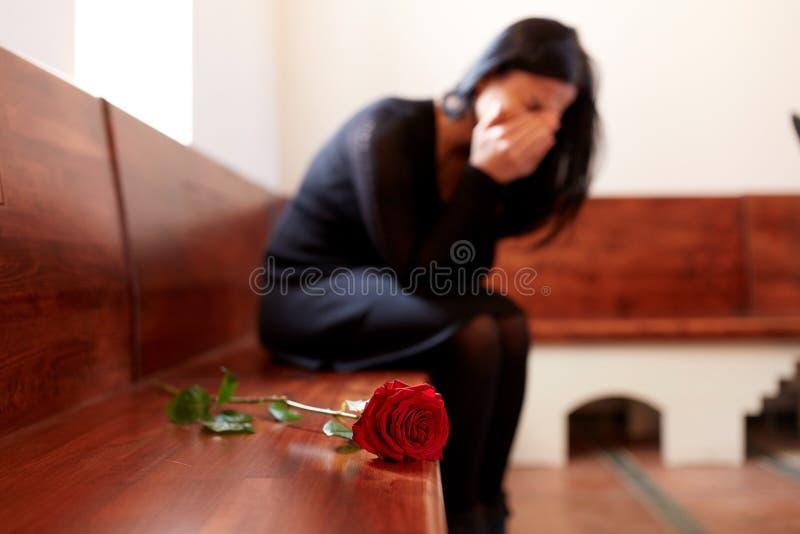 有红色玫瑰的哭泣的妇女在葬礼在教会里 库存图片