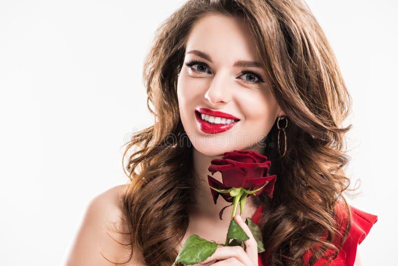 有红色玫瑰的微笑的可爱的女孩 免版税库存图片