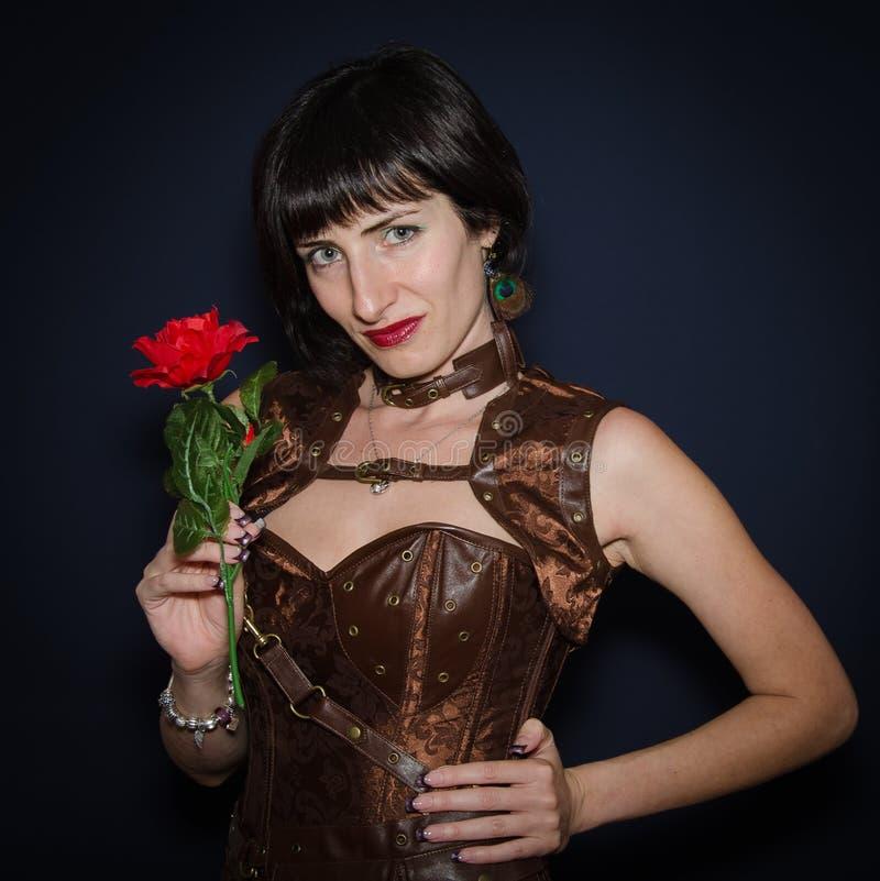 有红色玫瑰的深色的妇女 免版税库存图片