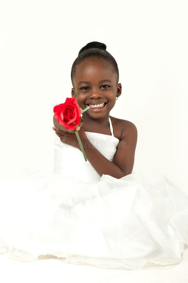有红色玫瑰的美丽的小女孩 图库摄影